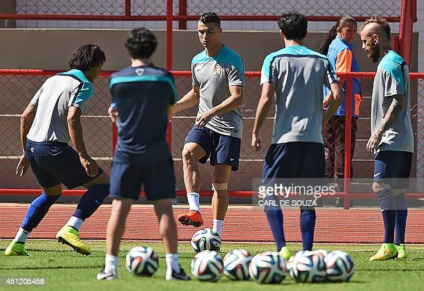 Portugal's forward Cristiano Ronaldo warms up with teammates during a training session in Brasilia on June 25 on the eve of the 2014 FIFA World Cup...