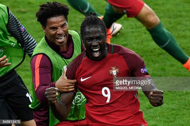 Portugal's forward Eder celebrates with Portugal's defender Eliseu after scoring a goal during the Euro 2016 final football match between Portugal...