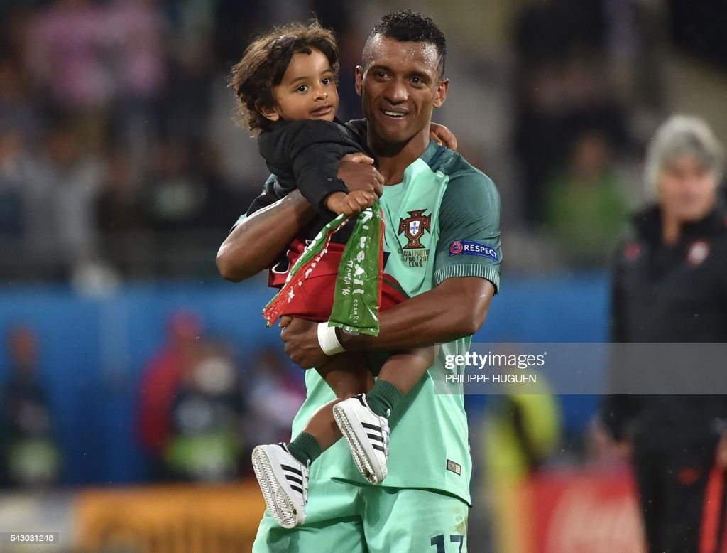 Portugal's forward Nani holds with his son Lucas at the end of the Euro 2016 round of sixteen football match Croatia vs Portugal, on June 25, 2016 at the Bollaert-Delelis stadium in Lens. / AFP / PHILIPPE