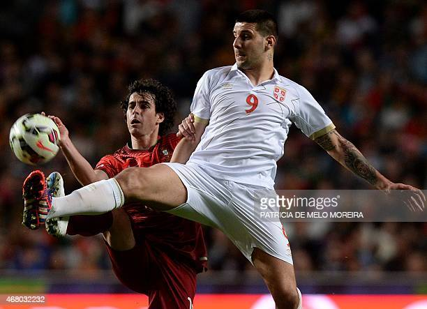 Portugal's forward Tiago Mendes vies with Serbian midfielder Aleksandar Mitrovic during the Portugal vs Serbia EURO 2016 qualifying football match at...