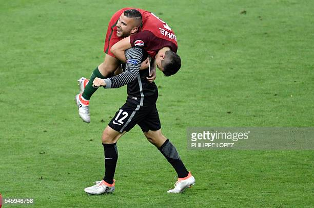 Portugal's goalkeeper Anthony Lopes and Portugal's defender Raphael Guerreiro celebrate the team's 10 win in the Euro 2016 final football match...