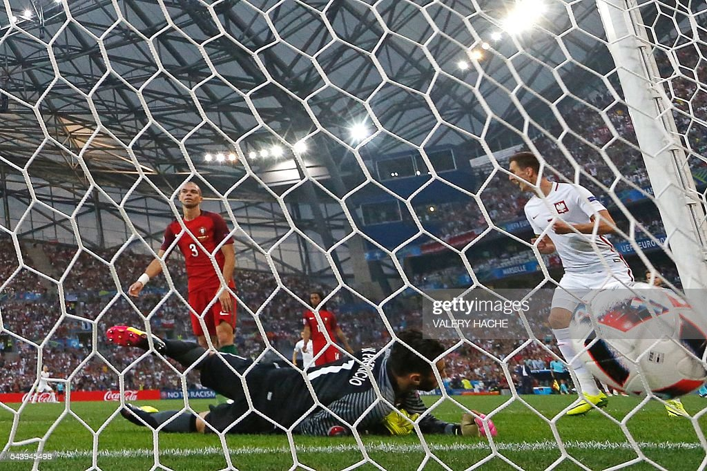 Portugal's goalkeeper Rui Patricio (C) takes the first goal during the Euro 2016 quarter-final football match between Poland and Portugal at the Stade Velodrome in Marseille on June 30, 2016. / AFP / Valery HACHE