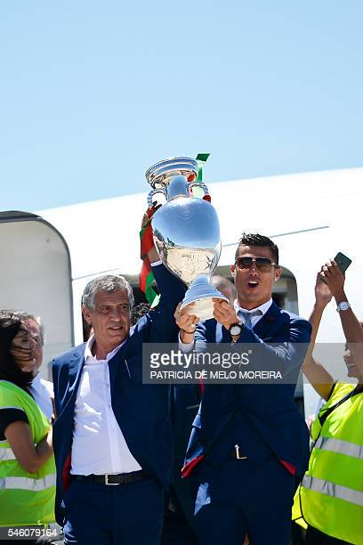Portugal's head coach Fernando Santos and Portugal's forward Cristiano Ronaldo hold the trophy on arrival at Lisbon airport on July 11 2016 after...
