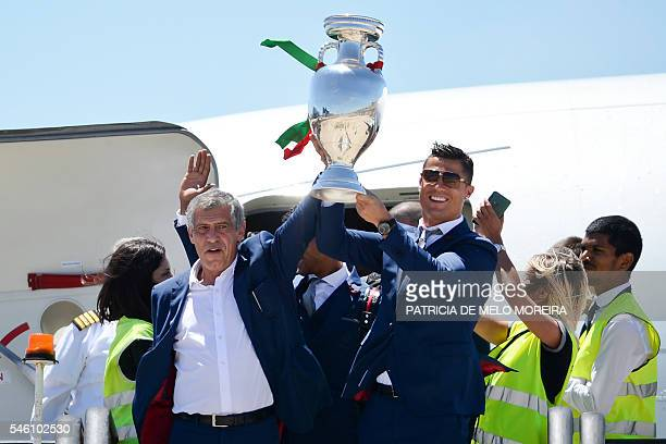 TOPSHOT Portugal's head coach Fernando Santos and Portugal's forward Cristiano Ronaldo hold the trophy on arrival at Lisbon airport on July 11 2016...