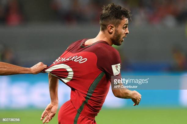 Portugal's midfielder Bernardo Silva is held by the shirt during the 2017 Confederations Cup semifinal football match between Portugal and Chile at...