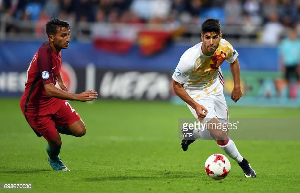 Portugal's midfielder Joao Carvalho Spain's midfielder Marco Asensio Willemsem vie for the ball during the UEFA U21 European Championship Group B...