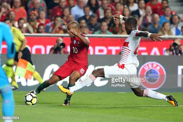 Portugal's midfielder Joao Mario vies with Switzerland's defender Johan Djourou during the 2018 FIFA World Cup qualifying football match between...