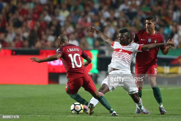 Portugal's midfielder Joao Mario vies with Switzerland's forward Breel Embolo during the 2018 FIFA World Cup qualifying football match between...