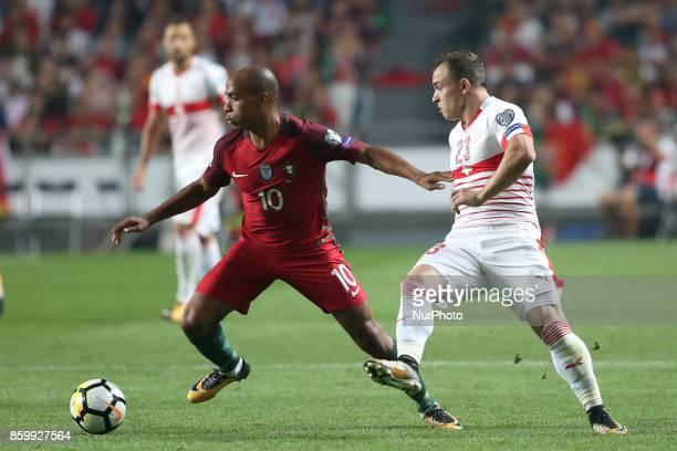 Portugal's midfielder Joao Mario vies with Switzerland's midfielder Xherdan Shaqiri during the 2018 FIFA World Cup qualifying football match between...