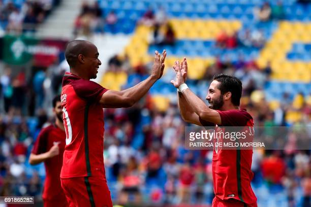 Portugal's midfielder Joao Moutinho celebrates with his teammate Portugal's midfielder Joao Mario after scoring during the friendly international...