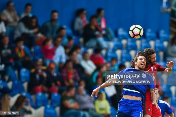 Portugal's midfielder Joao Moutinho heads the ball with Cyprus' defender Renato Margaça during the friendly international football match Portugal vs...