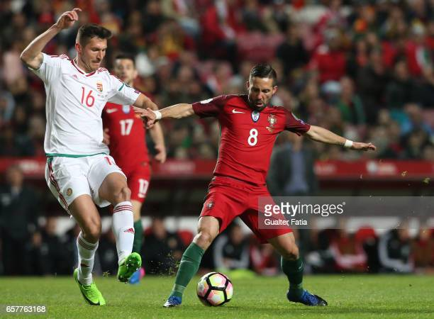 Portugal's midfielder Joao Moutinho with HungaryÕs defender Adam Pinter in action during the FIFA 2018 World Cup Qualifier match between Portugal and...