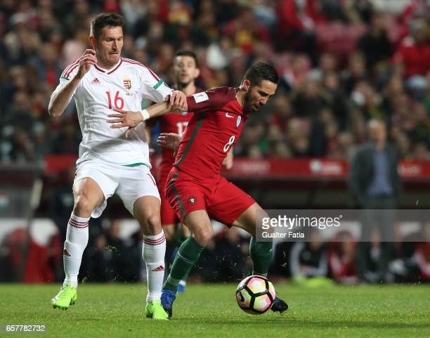 Portugal's midfielder Joao Moutinho with Hungary's defender Adam Pinter in action during the FIFA 2018 World Cup Qualifier match between Portugal and...