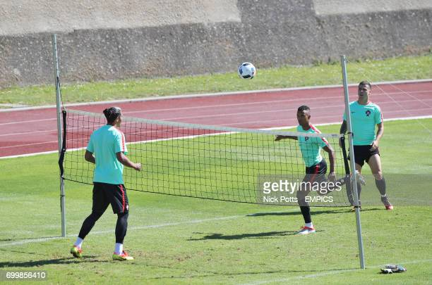 Portugal's Nani Bruno Alves and Vieirinha playing vollyball during a training session in Marcoussis Paris