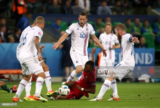 Portugal's Nani wins a free kick after going down under the challenge from Iceland's Gylfi Sigurdsson and Aron Gunnarsson