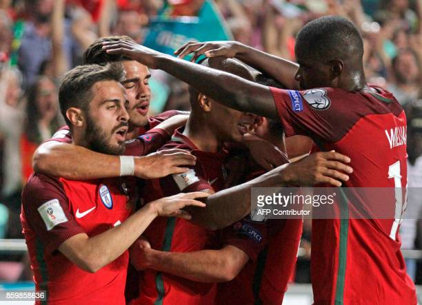 Portugals players celebrate after Switzerland's defender Johan Djourou scored an own goal during the FIFA World Cup 2018 Group B qualifier football...