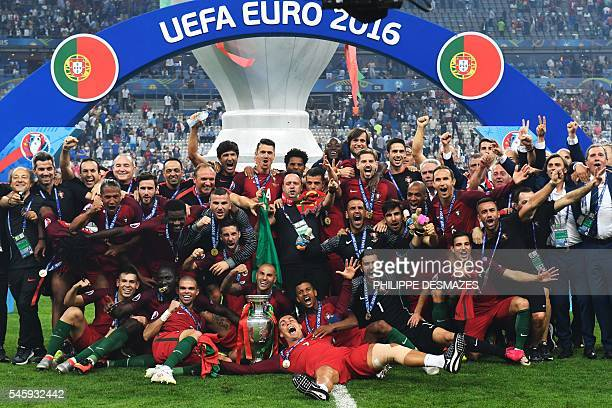 TOPSHOT Portugal's players pose with the trophy after they beat France during the Euro 2016 final football match at the Stade de France in SaintDenis...