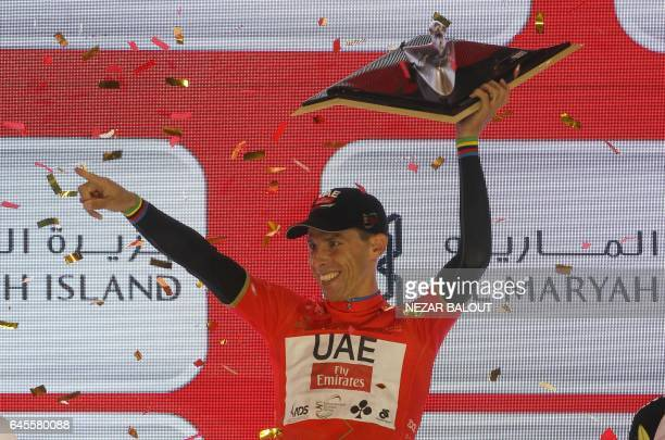 Portugal's Rui Costa wearing the overall leader red jersey celebrates on stage after winning the final Yas Island stage of the Tour of Abu Dhabi on...