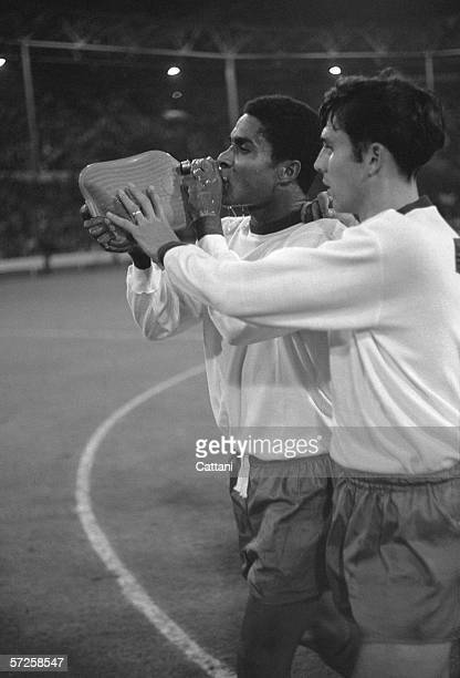Portugal's star goalscorer Eusebio takes a drink of water from a hot water bottle after beating Russia 21 at Wembley in the playoff for third place...