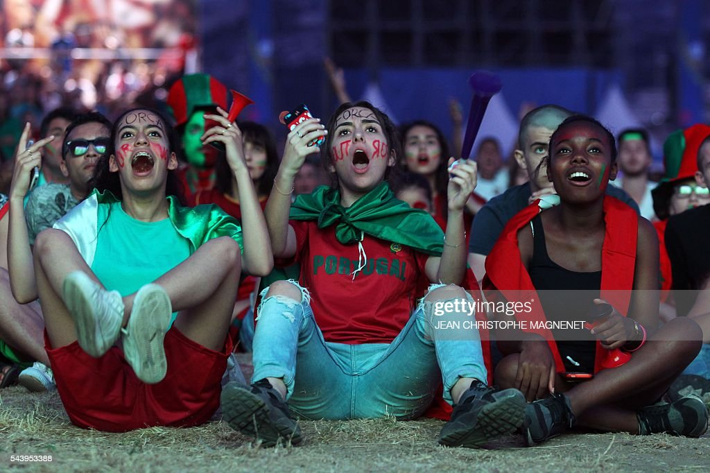 Portugal's supporters react as they watch on a giant screen the Euro 2016 championship match between Poland and Portugal at the Fanzone of Marseille, in Marseille, southern France, on June 30, 2016. / AFP / JEAN