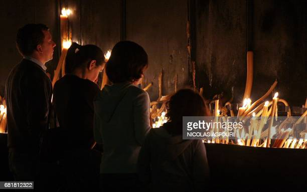 A Portuguese familly lights candles during a mass for the Pope in a chapel infront of the Basilic of Fatima 140 kilometers north of Lisbon 01 Avril...