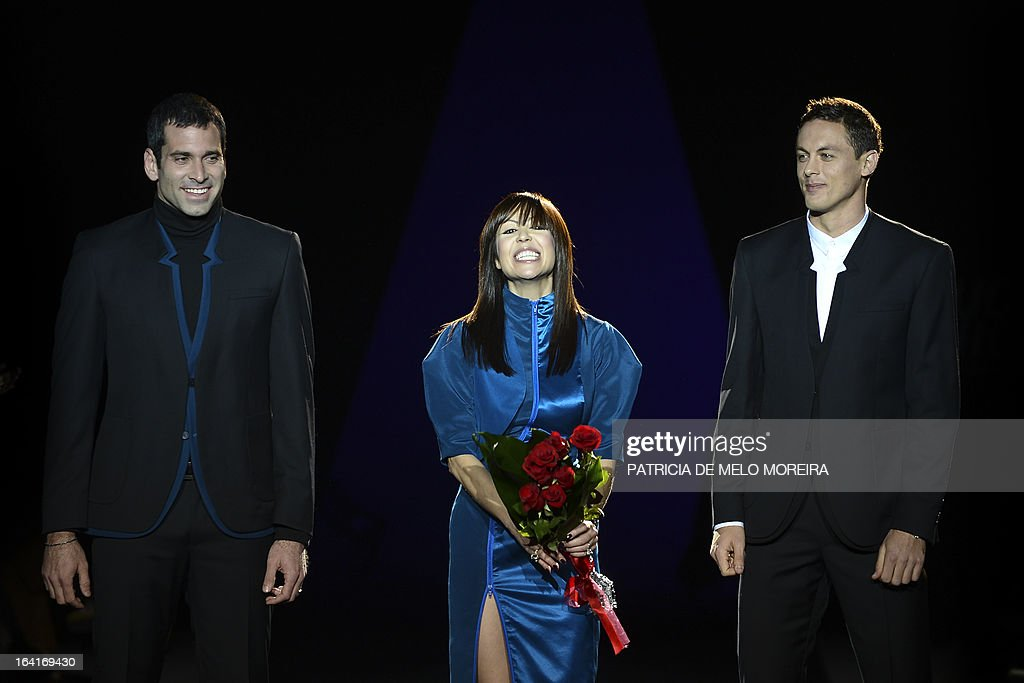 Portuguese fashion designer Fatima Lopes (C), flanked by Benfica's Brazilian goalkeeper Artur Moraes (L) Benfica's Serbian midfielder Nemanja Matic (R), acknowledges the audience at the end of her show during the 32nd Portugal Fashion at the Convento do Beato in Lisbon on March 20, 2013. AFP PHOTO / PATRICIA DE MELO MOREIRA