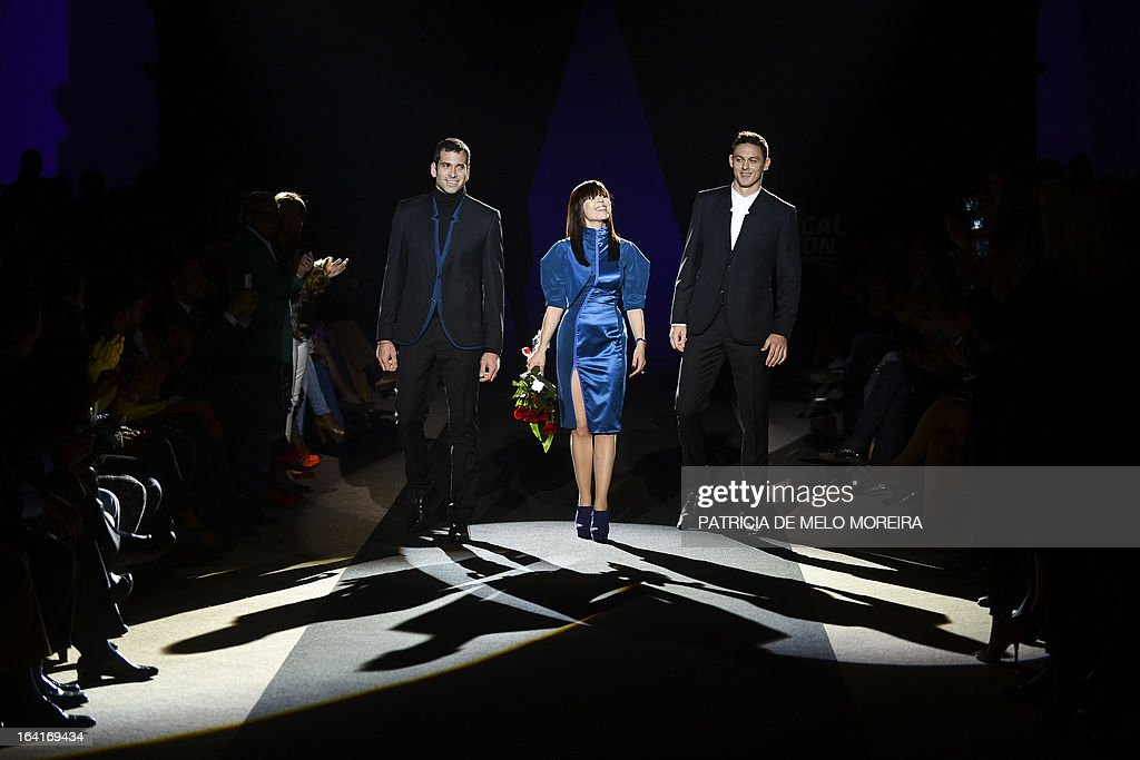 Portuguese fashion designer Fatima Lopes (C), flanked by Benfica's Brazilian goalkeeper Artur Moraes (L) Benfica's Serbian midfielder Nemanja Matic (R), acknowledges the audience at the end of her show during the 32nd Portugal Fashion at the Convento do Beato in Lisbon on March 20, 2013.
