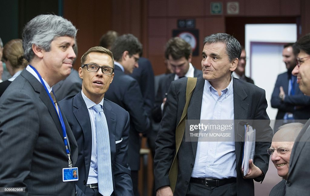 Portuguese Finance Minister Mário Centeno talks with Finnish Finance Minister Alexander Stubb, Greek Finance Minister Euclid Tsakalotos and German Finance Minister Wolfgang Schäuble prior to a meeting of Eurogroup ministers at the European Council headquarters in Brussels on February 11, 2016. / AFP / THIERRY MONASSE