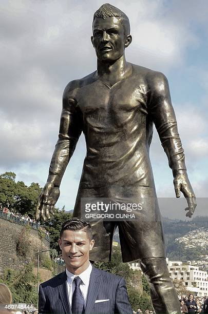 Portuguese football player Cristiano Ronaldo from the Real Madrid poses beneath a statue of himself during the unveling ceremony in his hometown in...