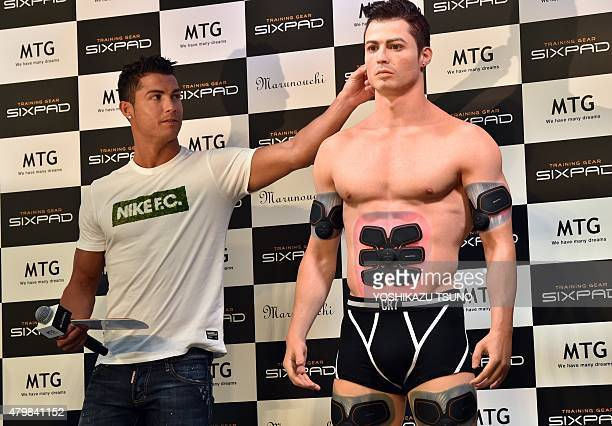 Portuguese football star Cristiano Ronaldo touches his lookalike figure made by a 3D printer during a promotional event in Tokyo on July 8 2015...