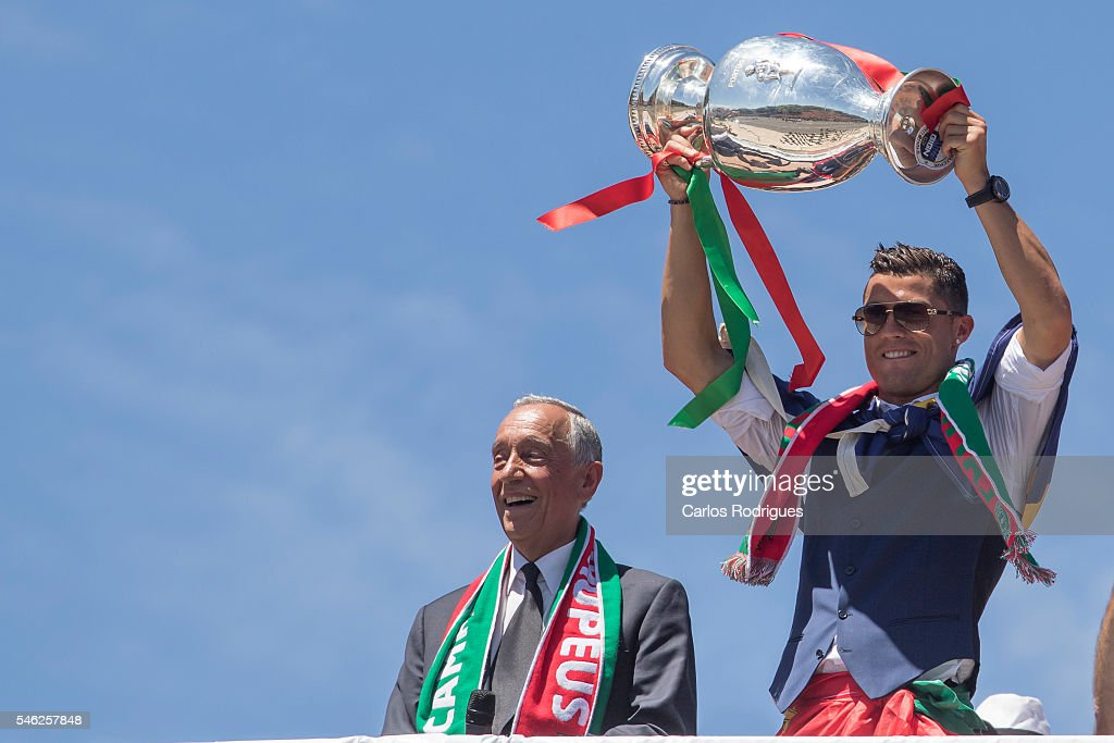 Portuguese forward Cristiano Ronaldo (R) and Portuguese President Marcelo Rebelo de Sousa (L) showing the European cup to the supporters during the meeting with the Portuguese President Marcelo Rebelo de Sousa for the Portugal Euro 2016 Victory ceremonies at Lisbon on July 11, 2016 in Lisbon, Portugal.