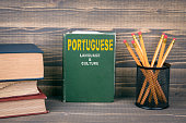 Portuguese language and culture concept. Book on a wooden background