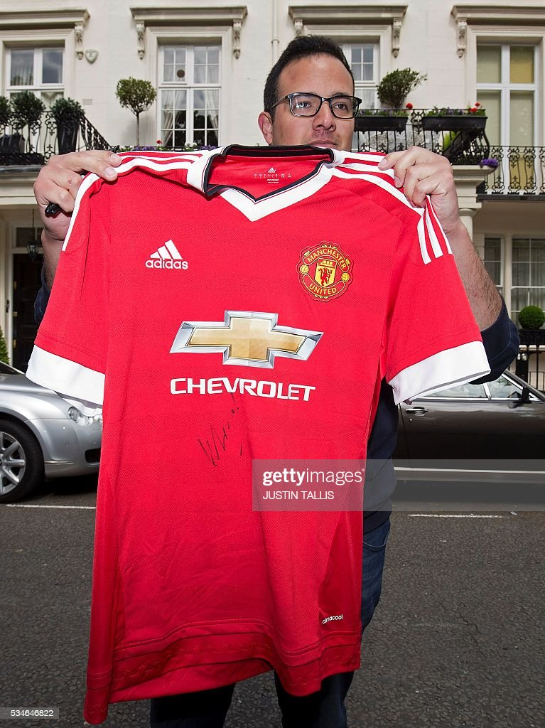 Portuguese Manchester United fan, Steven Ribeiro, poses with the Manchester United football shirt that the team's new manager, Jose Mourinho, signed for him, as Mourinho left his home in central London on May 27, 2016. Manchester United on Friday anointed Jose Mourinho as their new manager to launch a third bid in less than three years to transform the Red Devils into a title-winning force again. After three days of talks, Mourinho agreed a three-year contract on a bumper salary reportedly worth more than $20 million (19.5 million euros) a year. / AFP / JUSTIN