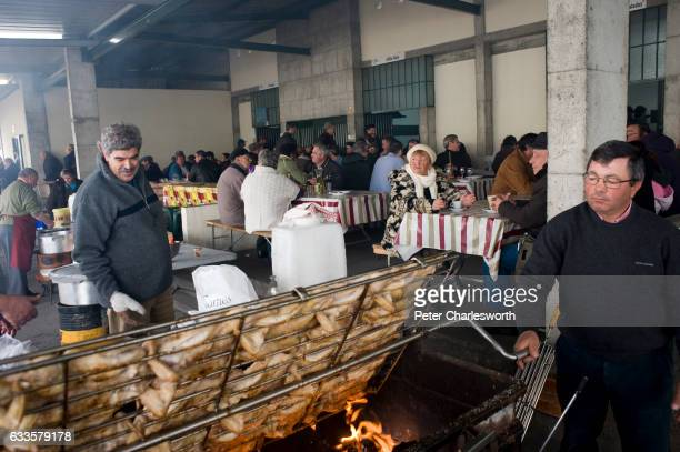 Portuguese men cook chickens over a large barbecue pit at the Sunday market in the small provincial town where diners enjoy the typical Portuguese...