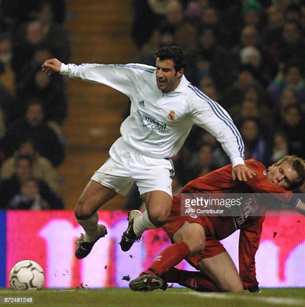 Portuguese player of Real Madrid Luis Figo is tackled by Kvarne of Real Sociedad during the first division football match in Madrid 15 December 2001...