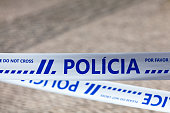 """Police tape with written in it in Portuguese """"Polícia""""."""