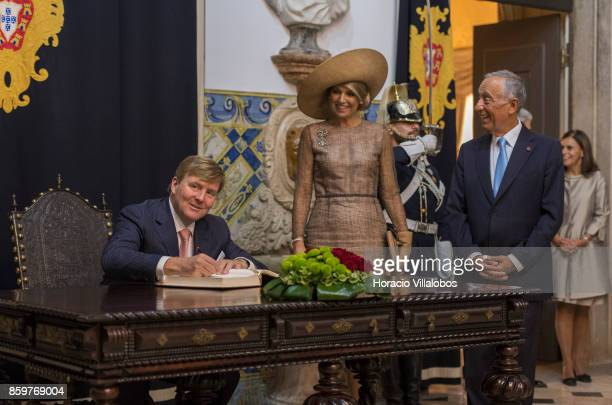 Portuguese President Marcelo Rebelo de Sousa and Queen Maxima of The Netherlands watch King WillemAlexander of The Netherlands signing the honor book...
