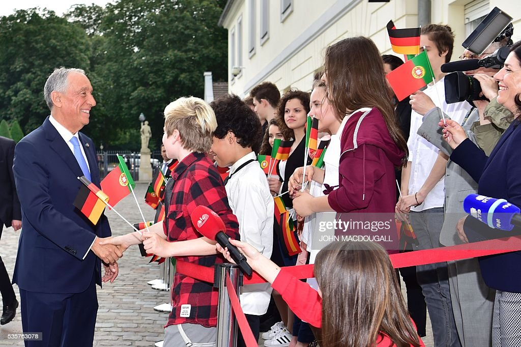 Portuguese President Marcelo Rebelo de Sousa (L) is greeted by youth waving with national flags as meets German President for talks at the Bellevue presidential palace in Berlin on May 30, 2016. / AFP / John MACDOUGALL