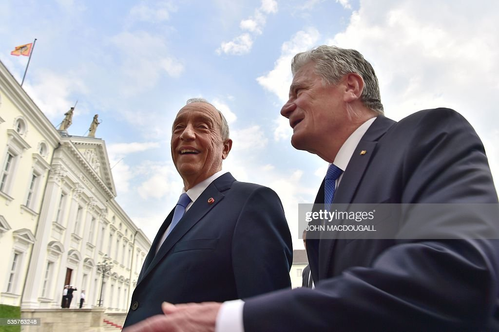 Portuguese President Marcelo Rebelo de Sousa (L) speaks with German President Joachim Gauck as they walk in the gardens of the Bellevue presidential palace in Berlin on May 30, 2016. / AFP / John MACDOUGALL