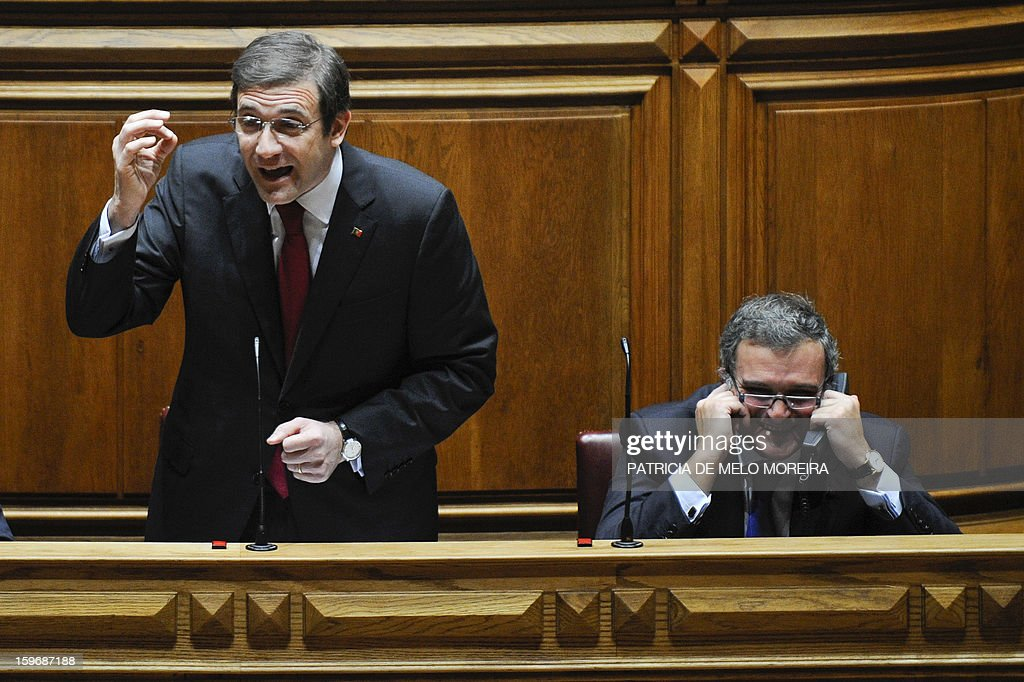 Portuguese Prime Minister Pedro Passos Coelho (L) gestures as he speaks next to Portuguese Minister of Parliamentary Affairs Miguel Relvas during a plenary session at the Parliament in Lisbon, on January 18, 2013. AFP PHOTO/ PATRICIA DE MELO MOREIRA
