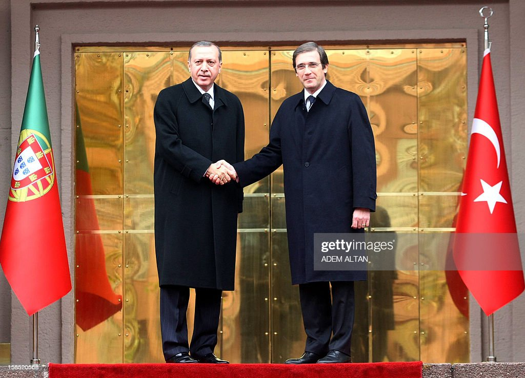Portuguese Prime Minister Pedro Passos Coelho (R) shakes hands with Turkish Prime Minister Recep Tayyip Erdogan (C) as they review an honour guard during a welcoming ceremony in Ankara on December 18, 2012. AFP PHOTO/ADEM ALTAN