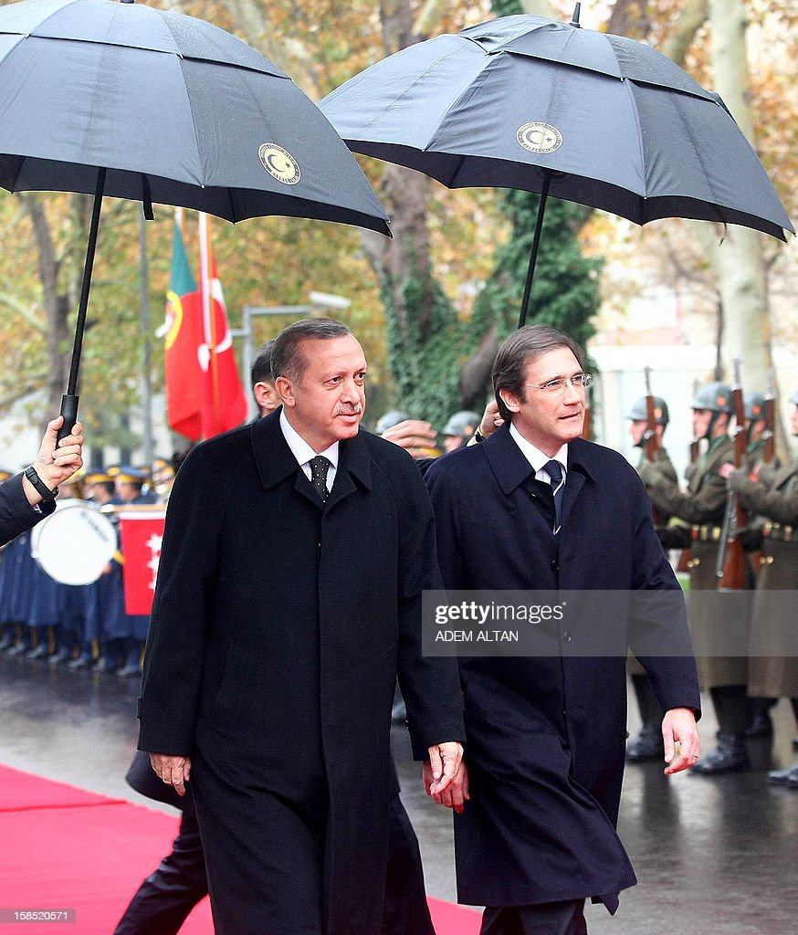 Portuguese Prime Minister Pedro Passos Coelho (R) walks with Turkish Prime Minister Recep Tayyip Erdogan (C) as they review an honour guard during a welcoming ceremony in Ankara on December 18, 2012. AFP PHOTO/ADEM ALTAN