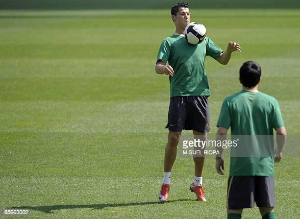 Portuguese striker Cristiano Ronaldo attends a training session next his teammate Anderson De Souza 'Deco' at the Dragao Stadium in Porto on March 27...