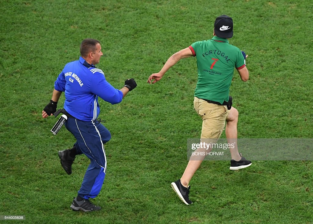 A Portuguese supporter invades the pitch during the Euro 2016 quarter-final football match between Poland and Portugal at the Stade Velodrome in Marseille on June 30, 2016. / AFP / BORIS