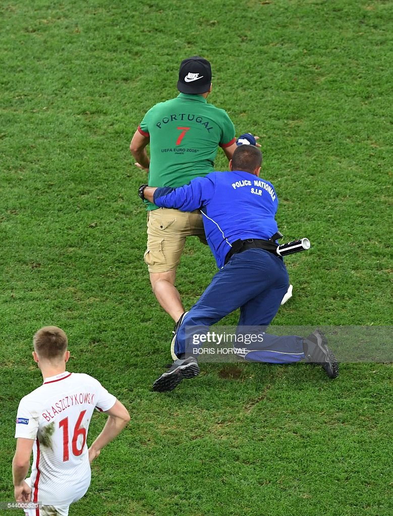 A Portuguese supporter is arrested by a French policeman after invading the pitch during the Euro 2016 quarter-final football match between Poland and Portugal at the Stade Velodrome in Marseille on June 30, 2016. / AFP / BORIS