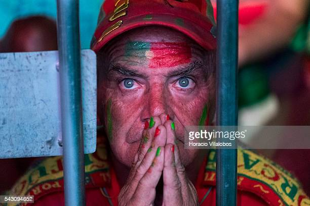 Portuguese supporter prays for the national soccer team victory while watching it playing against Croatia for Eighthfinals of UEFA Euro 2016 on a...