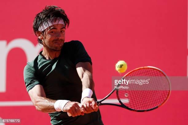 Portuguese tennis player Gastao Elias returns the ball to Tunisian player Malek Jaziri during their Millennium Estoril Open ATP Singles 1st round...