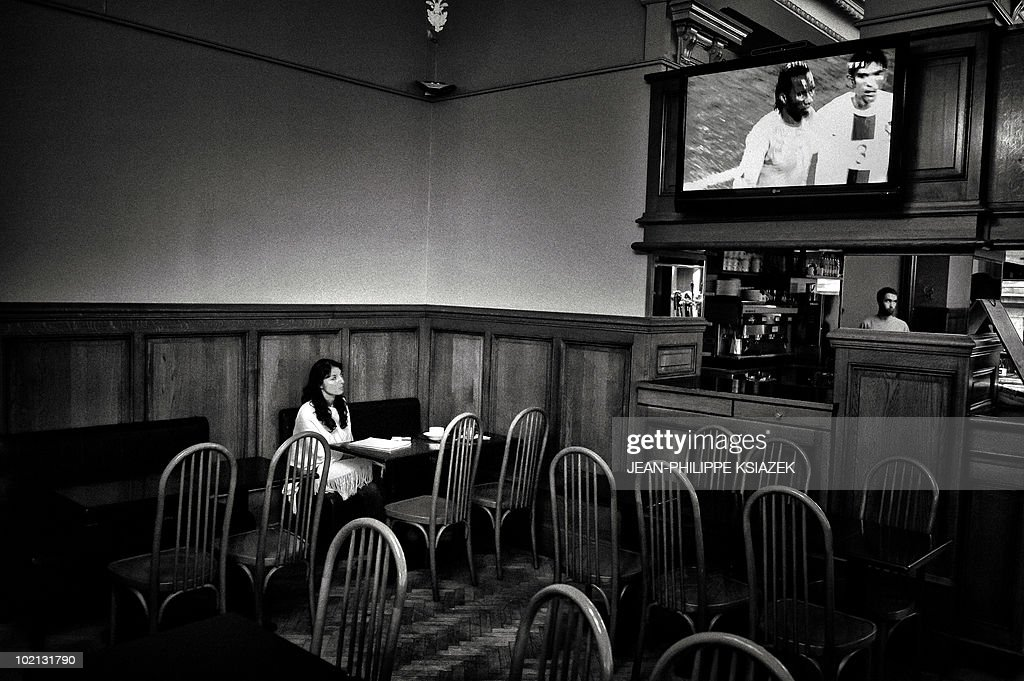 A Portuguese woman sits alone in a bar room as a TV broadcasts the 2010 World Cup Group G football match Ivory Coast vs. Portugal in the French central eastern city of Lyon on June 15, 2010. The match ended in a draw 0 -0.