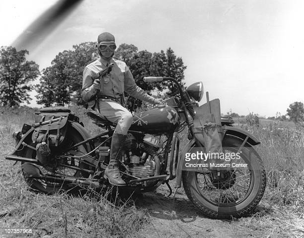 Posed portrait of a soldier on as he aims a machine gun while seated on a motorcycle emblazoned with logos from the the 1st Squadron 1st Cavalry...