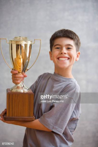 Posed portrait of boy holding trophy